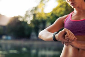 Femme la mise en place de la remise en forme montre intelligente pour courir. Sportive vérifier dispositif de surveillance. Banque d'images - 45175313