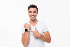 Portrait d'un doigt pointé gai homme souriant à la montre intelligente isolé sur fond blanc Banque d'images - 89637824