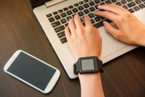Mains de femme portant smartwatch sur le clavier de son ordinateur portable femme travaillant sur ordinateur portable dans un café . modèle chinois chinois chinois Banque d'images - 76609201